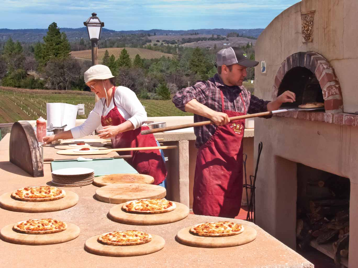 Photography: Woman and man making pizza with the view of the vineyard at a winery event